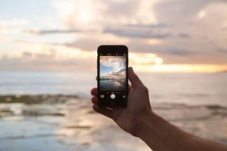 A smartphone taking a picture of a beautiful sunset which has been hopefully kept through Sustainable Practice in Telecoms