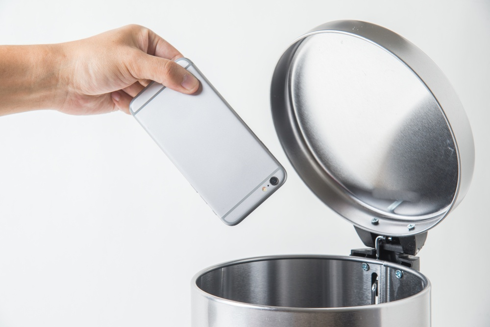 An iPhone about to go into the trash can symbolizing finding value in Mobile Device Retirement