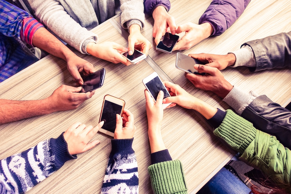 Many people using smartphones at a table showing the trends of Used devices and rising prices