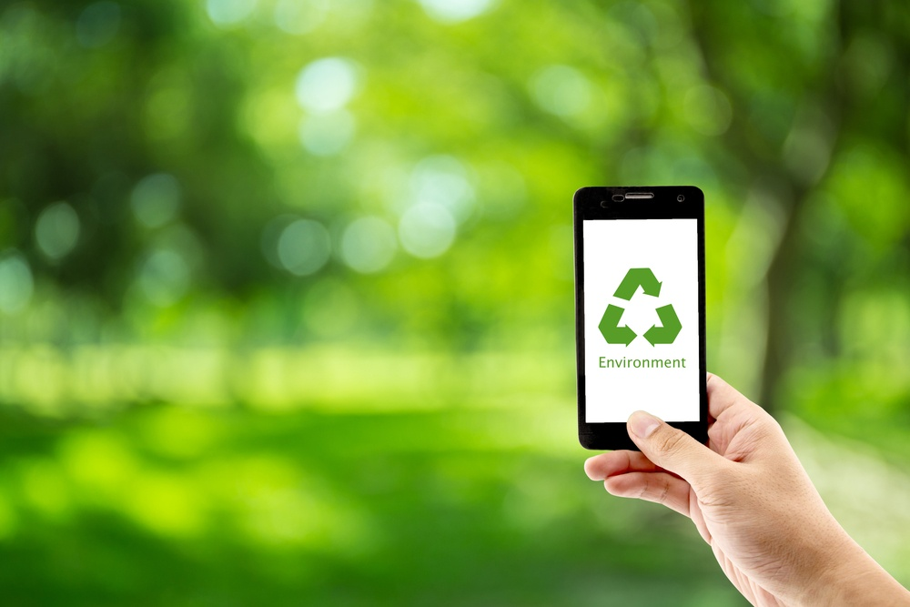 A picture of someone holding up a phone with a recycling symbol on the screen, asking the question: Mobile Recycling- Do You Know Where Your Phone is Going?