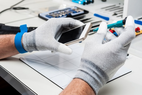 Image of a mobile phone repairman working on a device.